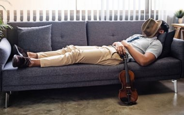 The handsome man laying down on sofa,put hat covered his face,sleeping,put violin beside sofa and touch with softly,relax time after practice,at studio