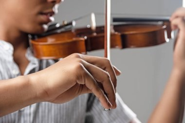 In selectve focus of human hand holding bow,showing how to  play violin,blurry light around