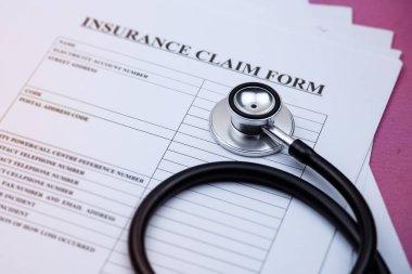 Head of stethoscope put on blurred insurance claim form,on background,blurry light around