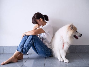 The stress woman sitting on ground floor,upset and unhappy emotion,the depressive disorder syndrome,unhealthy,sitting beside her dog