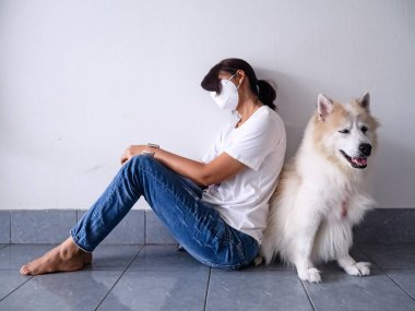 The illnesswoman wearing dust mask on her face,for protection from bad pollution,sitting on ground floor,beside cute dog,unhealthy emotion