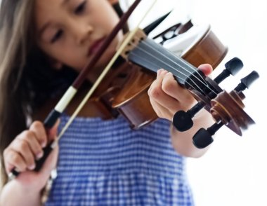 In selective focus of human hand pressing string of violin,show how to play the acoustic instrument,blurry light around