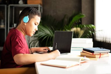 The young teenager wearing headphone for listening music,writing paper work,using laptop for searching data,blurry light around