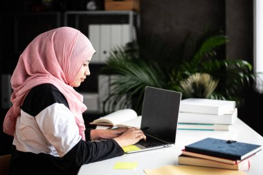 The beautiful muslim woman doing work at home,using laptop for searching data,with interested emotion,blurry light around