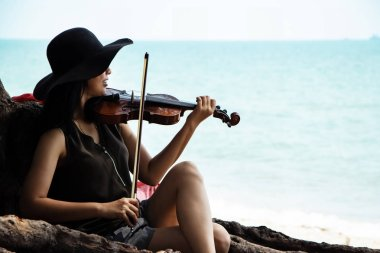 The beautiful woman playing violin on the beach,with smile and happy feeling,for relax time