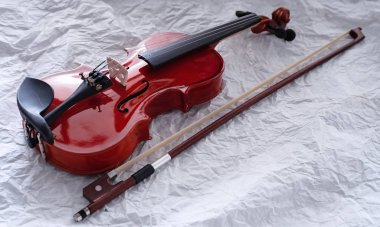 The classic violin and bow put on background,show body and part of acoustic instrument,blurry light around