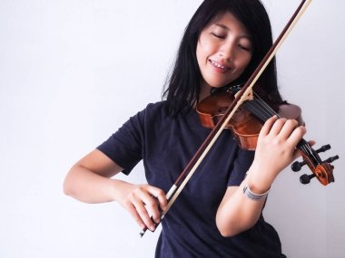 Woman playing violin with smile and happy feel,