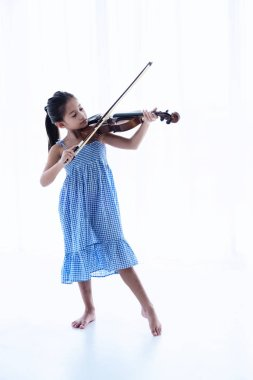 The little gril using bow touch on string of violin,show how to play acoustic instrument,on background,blurry light around