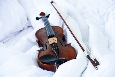 The classic violin and bow put on white blanket,show detail of stringed instrument,blurry light around