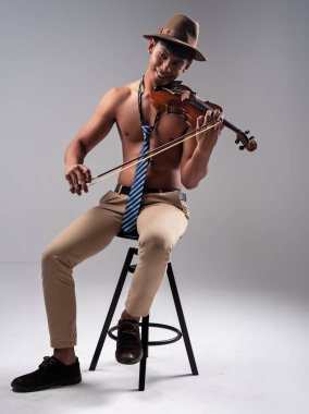 The handsome man wearing blue necktie and brown trousers,sitting on wooden chair,playing violin with smile and happy feeling