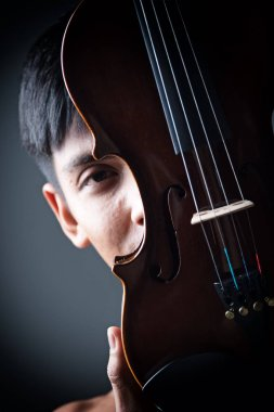 The abstract art design background of violin was holding by human hands,show front side of instrument,vintage and classic tone,blurry light around