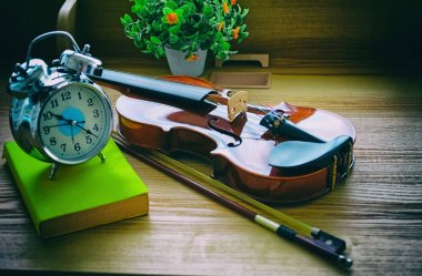 The abstract art design bakcgorund of violin and bow put beside alarm clock, on wooden desk,blurry light around