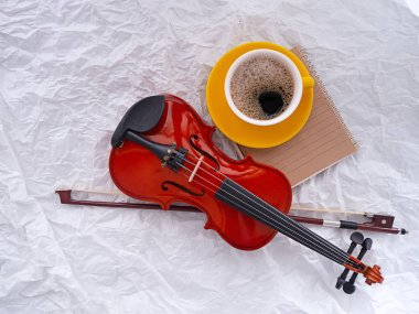 The wooden violin put beside yellow ceramic coffee cup,on grunge surface background
