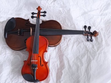The smaller violin put on bigger one,show detail and different size of acoustic instrument,on grunge surface background,blurry light around