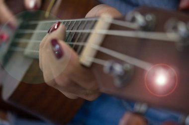 The blurry light design background of woman fingers playing ukulele,lens flare effect