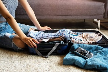 Hands of woman preparing cloths and accessories for holiday trip,packing a suitcase,at iving room,