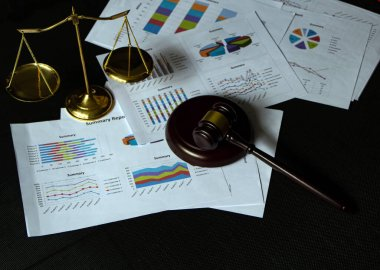 The wooden judge gavel ,brass scale and business paper chart put on black canvas background