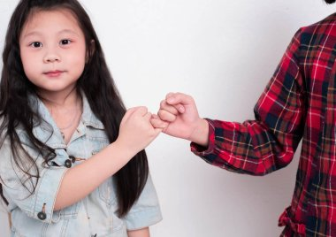 Little girl doing Pinky Swear with her sister,with happy feeling