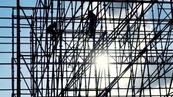 Arbeiter bei Sonnenuntergang montieren Konstruktionen. Silhouetten von Männern Ingenieur Arbeiter auf der Baustelle. Konzept Silhouette. Blauer Himmel. Baumaschinen. Kontrastprogramm.