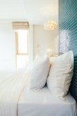Fotografie White pillow on bed decoration in hotel bedroom interior