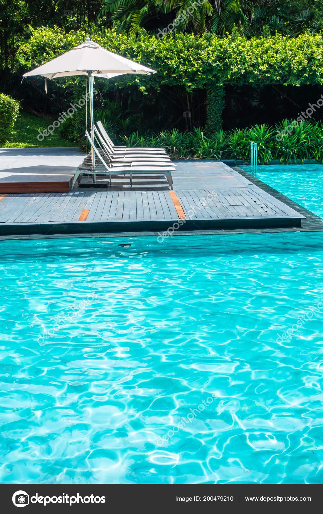 parapluie luxe magnifique chaise autour une piscine dans hôtel