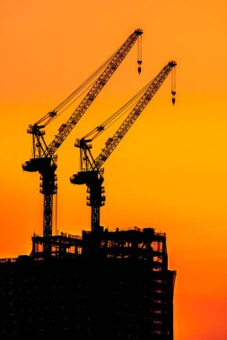 Beautiful Silhouette crane under construction building at sunset time