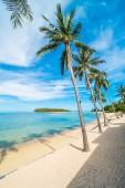 Nádherná tropická pláž moře a písek s kokosu palmou na modrou oblohu a bílé cloud pro cestování a dovolenou