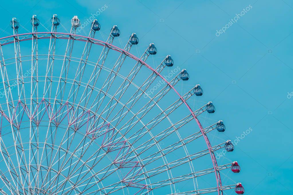 Ferris wheel in amusement festival park on blue sky background