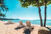 Nádherná tropická pláž a moře s židlí na modré obloze pro cestování a dovolenou