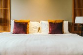 Fotografie Comfortable pillow on bed with light lamp furniture decoration interior of hotel bedroom