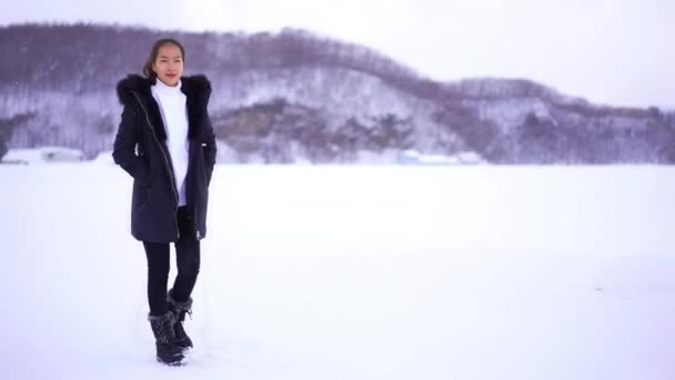 footage of beautiful Asian young woman under snowfall