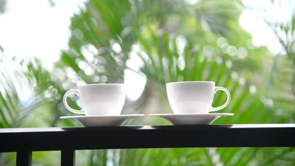 close-up footage of cups of coffee standing on balcony in front of nature background