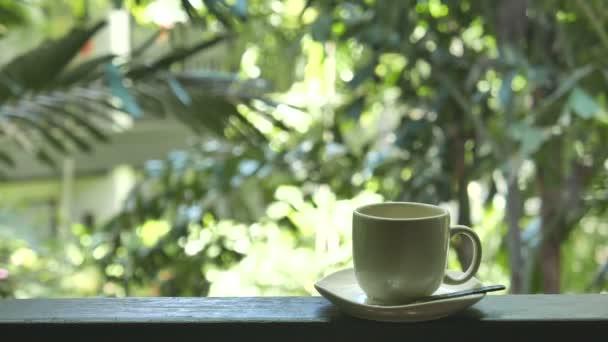 záběry šálek kávy stojící na balkóně před přírodním pozadím