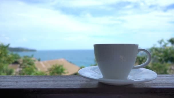 close-up footage of cup of coffee standing on balcony in front of nature background