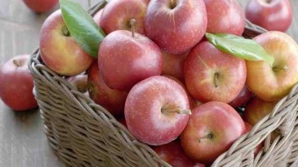 close-up footage of red apples in basket on wooden table