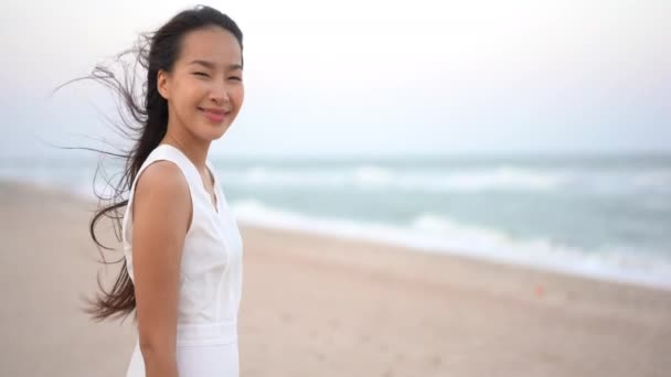 footage of Asian woman on seashore during summer vacation