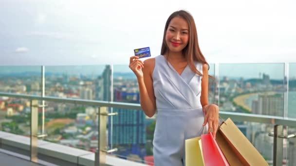 záběry nádherné asijské ženy nakupaholic s kreditní kartou a nákupními sáčky
