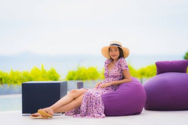Portrait beautiful young asian woman looking at sea ocean with h