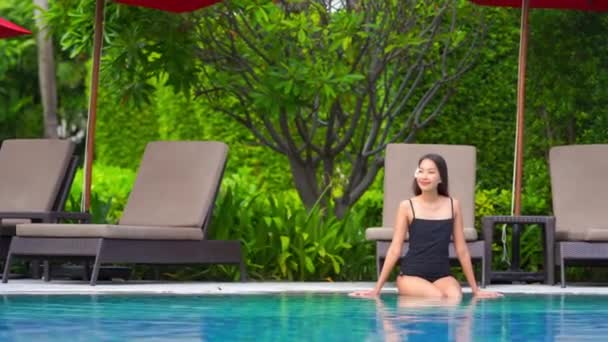 footage of beautiful asian woman relaxing in pool at hotel