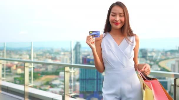 felvétel gyönyörű ázsiai nő hitelkártyával és bevásárló táskák