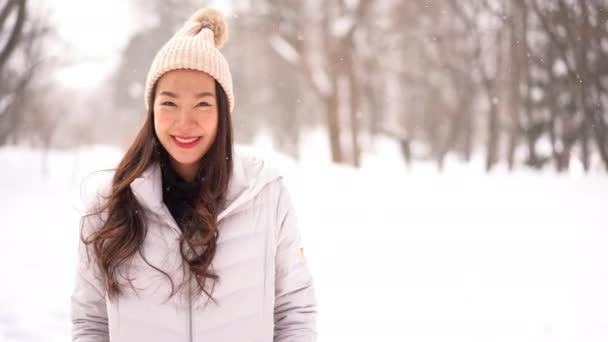 záběry krásné asijské ženy v teplém oblečení stojící venku pod sněhem