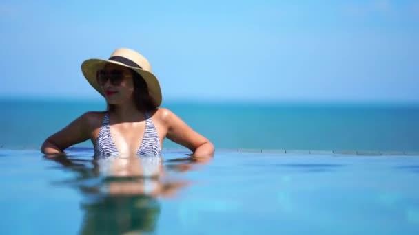 záběry asijské ženy relaxační v bazénu v letních prázdninách