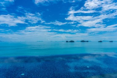 Beautiful outdoor swimming pool with sea ocean on white cloud bl