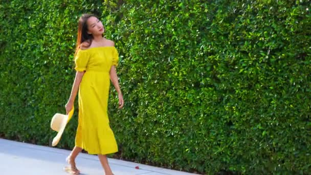 footage of beautiful Asian woman in yellow dress in front of green bush