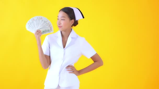 footage of beautiful asian female doctor holding bunch of cash on yellow
