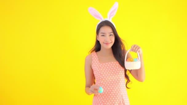felvétel gyönyörű ázsiai nő nyuszifül és kosár húsvéti tojás