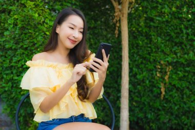 Young asian woman using smart mobile phone around outdoor nature view
