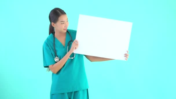 footage of beautiful asian female doctor holding blank white board on blue