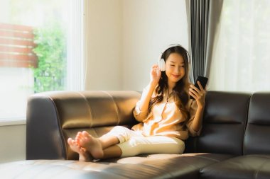 Portrait beautiful young asian woman use smartphone or cellphone on sofa with headphone for listen music
