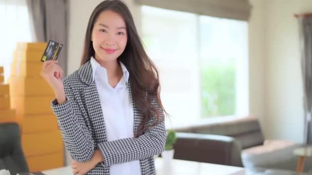 záběry krásné asijské podnikatelky s kreditní kartou v kanceláři